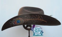 The original Sassy Cactus hat, our Rhinestone Peacock Feather Bling Straw , has been updated once again in a felt hat design in Swarovski rhinestones and hand painted glitter. Both sides of the brim o