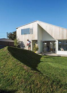 New Zealand house with angular cedar facade with cutaway