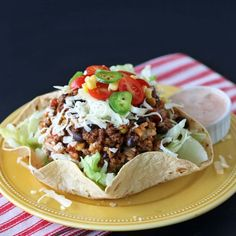 Flour tortilla bowl filled with lettuce, ground beef, corn, black beans and cheese.