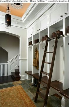 Floor-to-ceiling mudroom storage with a library ladder on a rail for access to upper cabinets and shelves.