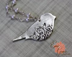 This fine silver floral bird necklace is a show stopper. The delicate filigree pattern in the bird is oxidized to a lovely dark color to bring out the design. The bird is suspended from a row of white freshwater pearls and a delicate sterling silver chain. The bird is handmade using precious metal clay that is fired leaving the end result of only fine silver (.999), all other pieces are fully sterling silver (.925). Necklace arrives neatly packaged and ready to wear and enjoy, or give as a…