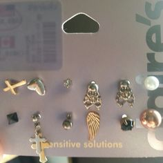 Mulitple earings Gold cross, silver heart, diamond, two silver skulls, pearl, black stud, silver ball, gold wing, black diamond, chrome ball. Never worn Claire's Jewelry