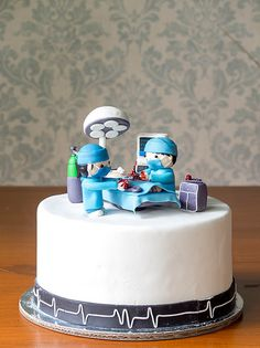 """We went kinda crazy with the hearts and scalpels on this Surgeon cake. We even put sweat on the surgeons thinking that no one would notice, but I guess people do notice these things! Hehe."""