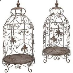 Set of 2 distressed metal birdcage terrariums with open scrollwork detail. Product: Small and large terrariumConstruction Material: Metal Color: White-washed brown Features: Fleur-de-lis and scrollwork details Dimensions: Small: 24 H x 12 Diameter Large: 28 H x 14 Diameter