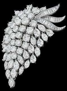 Here is a splendid platinum pin from the 1950's. The pin is set with approximately 12ct of sparkling marquise and pear cut diamonds. These diamonds are accentuated by approximately 1.15ct of baguette cut diamonds and approximately 4.85ct of round cut diamonds. The color of the diamonds is G-H with VS1 clarity. The measurement of the pin is 53mm by 37mm and it weighs 25.3 grams. This pin may also be worn as a pendant.