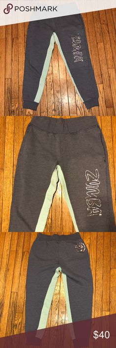 """Zumba Sweatpants Grey w/Light Blue Unisex M Zumba Sweatpants Grey w/Light Blue Unisex size Medium. The tag was itchy so it was cut out. These were in the men's collection, a size M, but they seem to fit more like a women's M, similar fit VS Joggers in a M. In excellent condition, side pockets banded ankles and waist. Grey with light blue on the inside of the legs and silver Zumba graphics. Super cool and very rare. Measures about 28"""" inseam, 38"""" Top-Bottom, 16"""" Waist (laying flat). No Flaws…"""