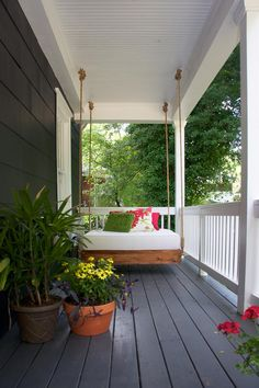 Potted plants serve two purposes in an outdoor living space: They add a splash of color, and they provide privacy for seating areas. On this porch, a few potted plants offer shelter for a daybed-style swing. Plus, the greenery coordinates with the colors of the throw pillows, tying everything together.