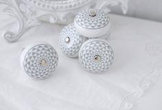 33 kr  Vit rund porslins knopp med grått retro mönster små rutigt. Med silver färgad metall stomme. I grepp vänlig modell.