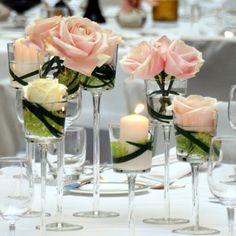 Decoração de mesa com taças e rosas.