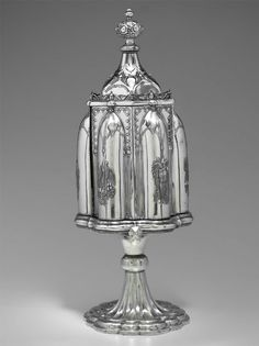 """Marked """"PATENTED DEC. 1 1857"""" in arch at top. Doors revolve open with a twist of the knob, revealing glass cruet bottles in interior compartments."""
