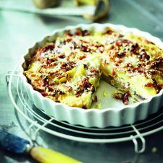Kook de aardappelen in circa 15 minuten net gaar. Laat ze enigszins afkoelen en pel ze. Snijd ze in dunne plakken. Bak ondertussen de spekblokjes met de tijm en uiringen knapperig. Voeg de knoflook toe en fruit nog enkele minuten. Beboter een ovenschaal of eenpersoons schaaltjes. Ver-warm de oven voor op 180°C. Leg de helft van de aardappelplakjes in de ovenschaal en strooi er wat zout en peper over. Verdeel de helft van de spekblokjes en ui erover. Vervolg met de rest van de…