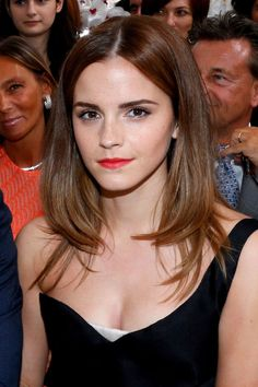 Try parting your hair down the middle and blow-drying straight, curling inwards towards the ends for a style like Emma's. Now if only we could figure out how to get those brows...