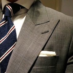 Light grey suit with peak lapels, white shirt, navy shantung tie with white & red stripes