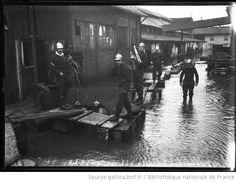 25/1/1910, incendie Pagès-Camus [pompiers en uniformes marchant sur des planches] : [photographie de presse] / [Agence Rol]