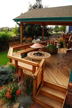 Redwood deck with built-in seating and fire pit. Designed by Outdoor Design