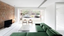 In a Montreal home, a minimal number of furnishings and exposed brick wall play nice with a refined, deep green sectional.