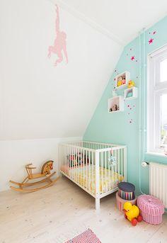 Un lit bébé blanc et un mur vert menthe