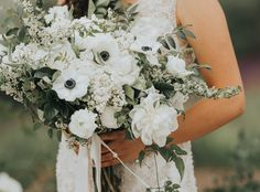 Beautiful in white, bridal bouquet with white lilacs, peonies and anemones, elegant lush wedding