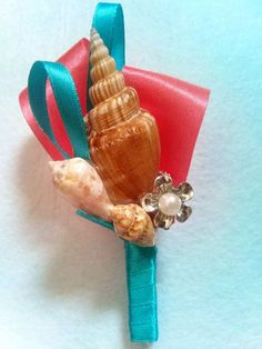 boutonniere for wedding beach theme - lighter blue, red ribbon, and white shells