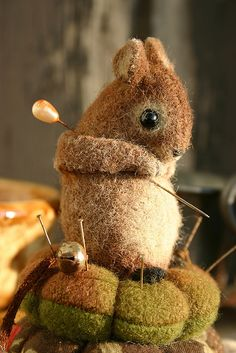 A Wee handpainted wool felt mouse sitting on two woolfelt pin cushions. 2008