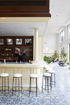 All-white bar + old-world wood & tiles = pure cocktail chic at the American Trade Hotel.