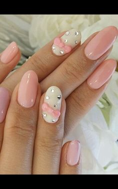 Pretty pink almond acrylic nails with white accents rinestones and bows