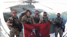 DEVGRU members from Red Squadron with their flag in front of a 160th SOAR MH-6.