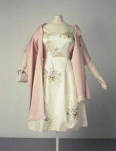 14-11-11  CMU  Trouwjurk met losse shawl (1954 – 1956 – midden jaren 1950)  Maison de Bonneterie. 001: mouwloze jurk met wijduitlopende rok van beige satijn. Met losse bloemmotieven geborduurd in kralen, borduurgaren en strass; 002: shawl: roze dubbelgestikte satijn met franjerand.