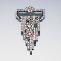 An art deco diamond and sapphire cascade brooch, circa 1925  The openwork geometric hanger composed of lines of single-cut diamonds and calibré-cut sapphires with an old brilliant and single-cut diamond flourish, issuing an articulated cascade, pierced with floral motifs and millegrain-set throughout with old brilliant, brilliant and single-cut diamonds and calibré-cut and cabochon sapphires, length 7.2cm.