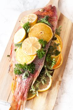 A Roasted Citrus & Herb Red Snapper stuffed with lemons, oranges and herbs is the perfect bright and light recipe for an easy, impressive weeknight dinner.