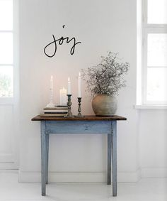 A gorgeous rustic looking hallway table decorated with candles, adds a nice bit of colour to the white room