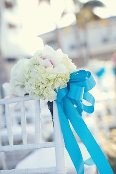 Love the bright ribbon combined with the hydrangea on the chair at this wedding