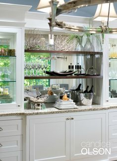A custom-built buffet answers the need for storage and service space.  Mirror backing across the entire top section reflects light and the beautiful outdoor view. #candiceolson