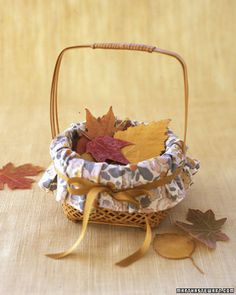 As a fitting nod to the season, substitute dried leaves for petals in your flower girl's basket. If fall foliage isn't abundant when you wed, you can order pressed leaves online (from drynature.com).We lined this pint-size basket with cotton fabric. Using scissors, cut a large round of fabric and a slit on opposite sides to accommodate handles, then place in basket. Wrap silk ribbon around, and tie in a bow.
