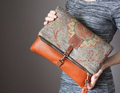 Fold over Clutch bag is made with a genuine cowhide and a gorgeous tapestry fabric. The clutch closes with a metal zipper and a trigger snap…