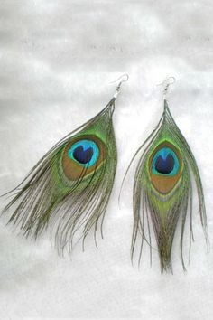 The earrings crafted in genuine feather, featuring oversized pendant, peacock feather detail and fish hook fastening. $13