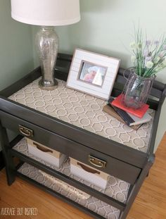A changing table was upcycled into a console table with gorgeous paint, new hardware, and fabric-lined shelves!