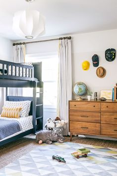 The boys' room was painted in various Benjamin Moore whites to create a subtle ombré effect. The navy-blue bunk bed is from Pottery Barn Kids, and the sideboard is West Elm.