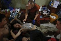 A Buddhist monk cleans the chest of Salut after adding another tattoo on his body at Wat Bang Phra in Nakhon Pathom province, about 80 km (50 miles) from Bangkok.