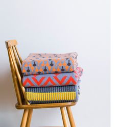 Blanket storage folded pretty on a simple chair to see and ready for use