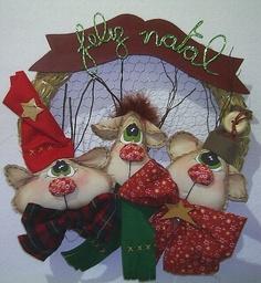 Guirlanda com enfeites de renas, confeccionadas em algodão cru pintado a mão, feltro e tecidos diversos de algodão. Medida: 30 cm de diametro.