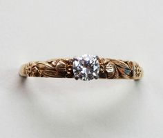 A 14 carat gold ring with a brilliant cut diamond set in platinum (app. 0.25 carats), the shank with floral decorations, signed: Tiffany & Co., circa 1930, in the original case. This ring is the antique version of 'The Tiffany Setting'.