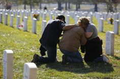 People grieve at a gravesite in Section 60, an area where members of the U.S. military who were killed in action in Iraq and Afghanistan are buried, during Veterans Day observances at Arlington National Cemetery in Arlington, Virginia, on November 11, 2012. (Reuters/Jonathan Ernst)