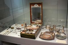 """Marie Antoinette's nécessaire described by biographer, Antoinia Frasier, as """"a kind of superior picnic basket made of beautiful, smooth walnut with a silver basin, tiny candlesticks and a teapot, which doubled as a dressing case, whose furnishings included little tortoiseshell picks as well as a mirror"""" (p. 323). [2nd of two pins]"""