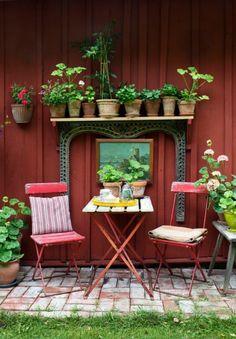 Både trädgård och inredning har fått växa fram med tiden. Hon tänker på gården som på en bostad och bygger rum med hjälp av krukor, möbler och blommor. – Jag tänker mycket på att skapa perspektiv och rum-i-rummet, säger hon. Den patinerade utemöbeln är köpt på auktion. Den ramas in av pelargoner och chili, vilket hjälper till att skapa ett rum i rummet.
