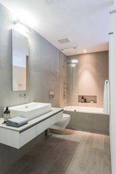 A contemporary, clean bathroom with wood-look porcelain flooring and light gray tile covering the walls. A lengthy vessel sink is perched atop the minimalist floating vanity with three drawers. A slim glass panel between the shower and toilet prevents water from splashing when the shower is on.