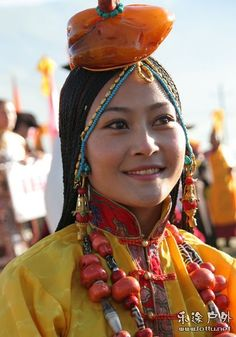 Young Khampa Tibetan Woman at Yushu Horse Festival dressed in the regional ceremonial style - she wear a huge amber bead on the crown of her head, tipped with coral, and two beautiful coral and replica dzi bead necklaces, and gold and coral earrings