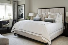 jennifer worts design inc neutral walls with white trim, padded headboard with dark wood frame, bedside tables and desk.  Love the chair at the desk and how the curtain and artwork complement each other.