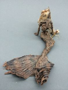 This auction is for a handmade dead mermaid . Poor little thing. I guess if there are real mermaids there would be dead ones as well. She seems to have been a queen or princess a long time ago having a crown and royal staff. She still holds onto her beauty even in her mummified state. She is about 3.5 tall and 8 across from tip of tail to her hair. She is made of artist materials and her hair is mohair. The myth of the mermaid could be within your reach. This is dead mermaid #101…