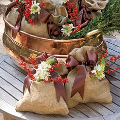 Place gifts in burlap sacks, tie with ribbon and adorn with Christmas picks or live Christmas pines and flowers.- The Enchanted Home